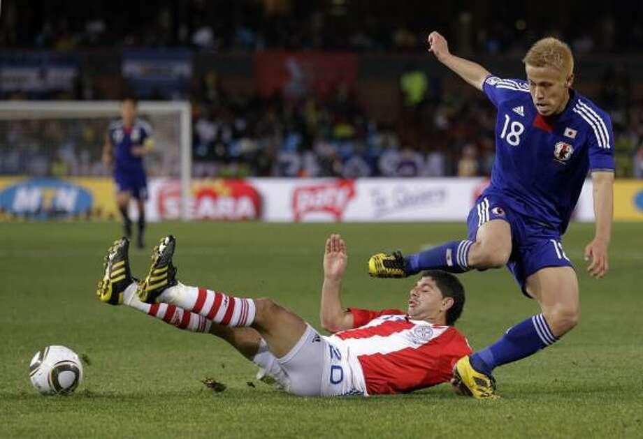El paraguayo Nestor Ortigoza (izq.) cae luego de una falta del jugador japonés Keisuke Honda. Photo: Luca Bruno, AP