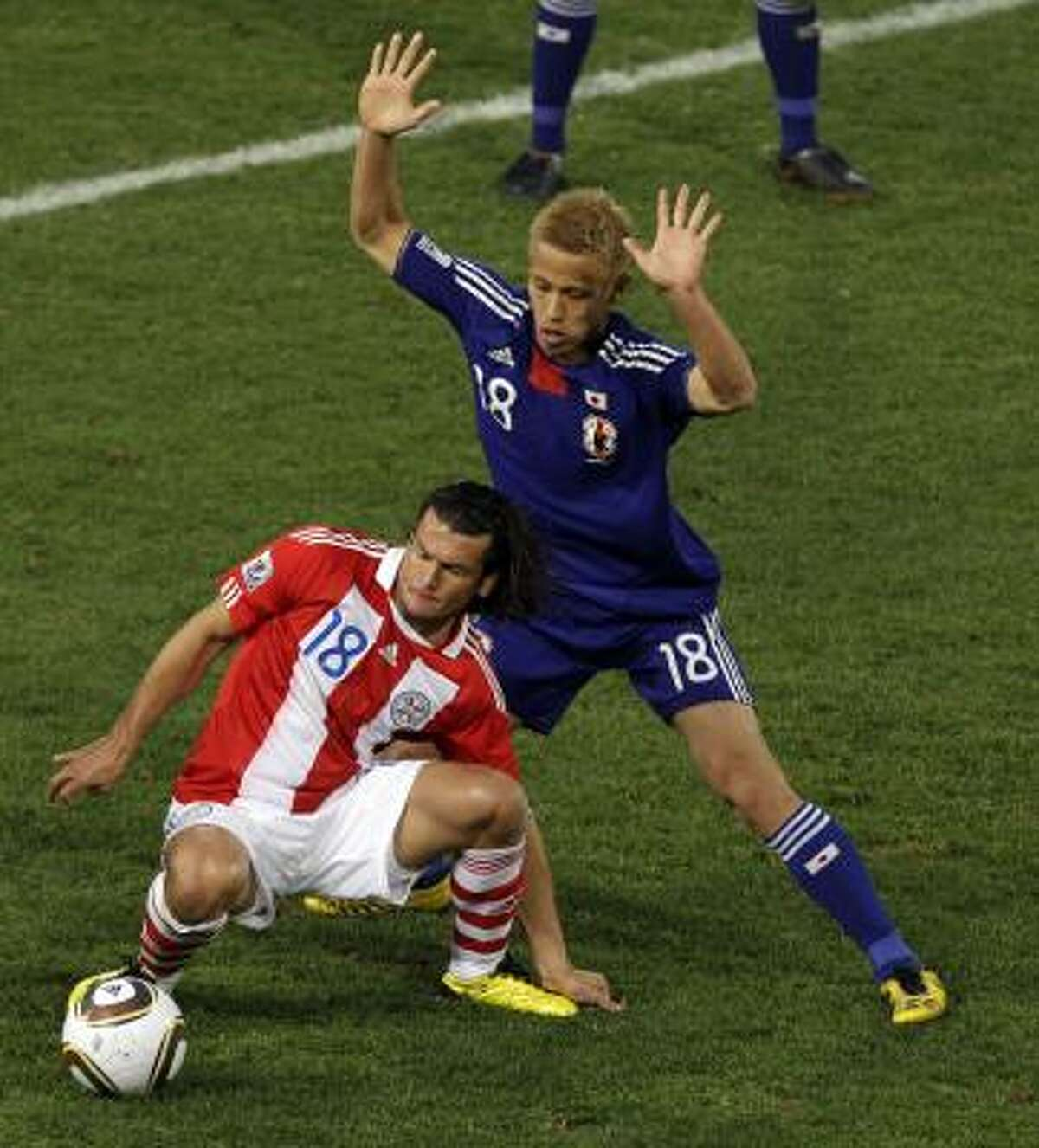 El atacante paraguayo Nelson Haedo Valdez (izq.) protege la pelota del japonés Honda.
