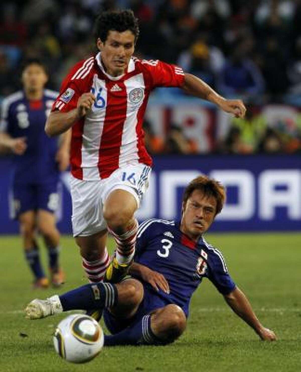 El paraguayo Cristian Riveros (izq.) se escapa de la barrida del defensa japonés Yuichi Komano.