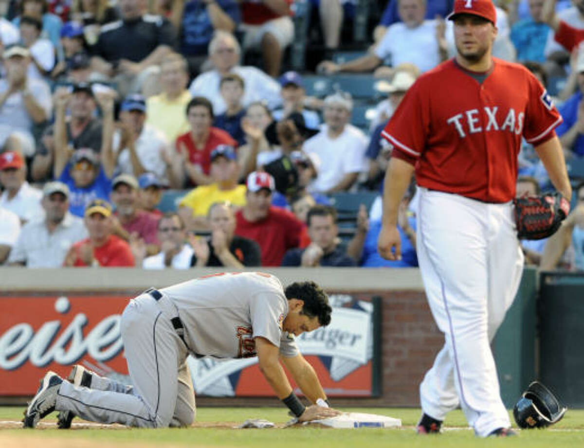 Houston's Oswaldo Navarro pauses at first base after being tagged out by Rangers shortstop Elvis Andrus in the third inning.