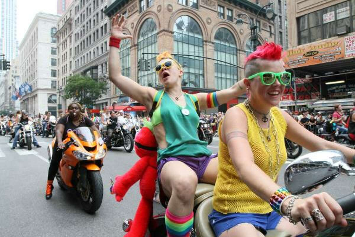 Jackie Carlson, second from right, and her partner Cara Lee Sparry, both from the Brooklyn borough of New York, make their way down New York's Fifth Avenue as they take part in the city's annual parade celebrating gay pride on Sunday, June 27, 2010.
