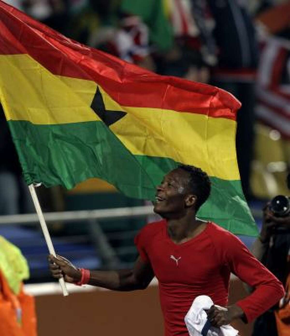 Ghana player John Pantsil runs with his country's flag at the end of the match.
