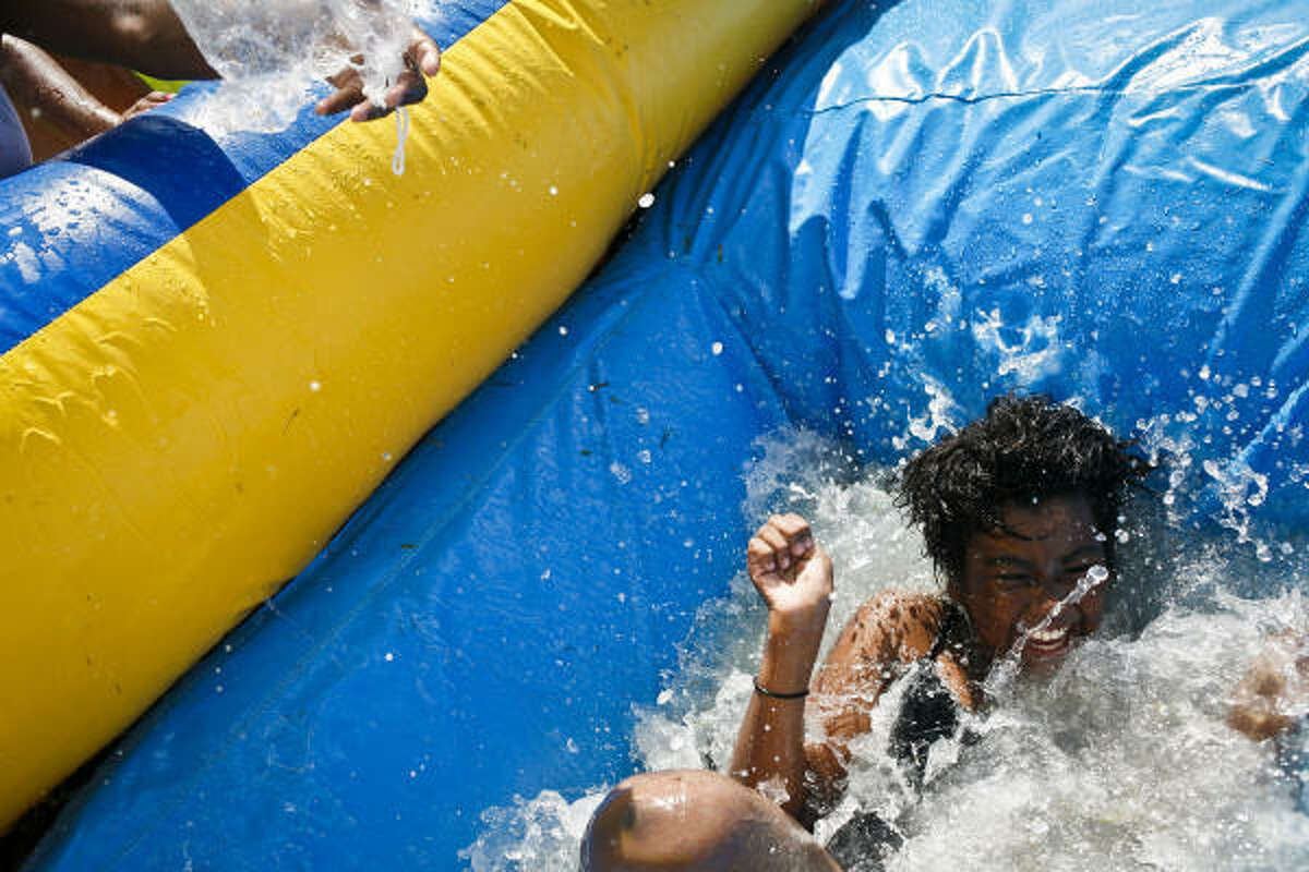 Jade King, 10, reacts as a cold bag of ice is dumped on her after sliding down an inflatable water slide during