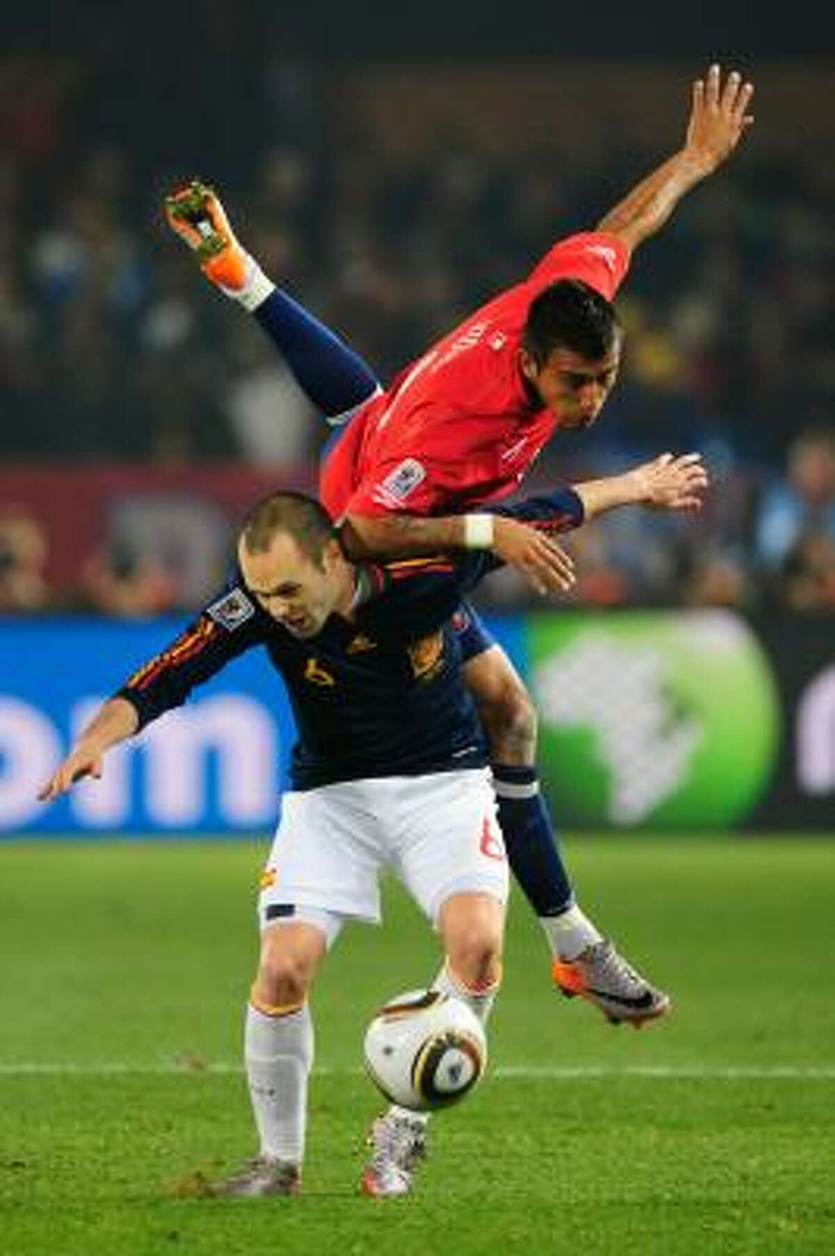 Arturo Vidal of Chile foes flying over Andres Iniesta of Spain.