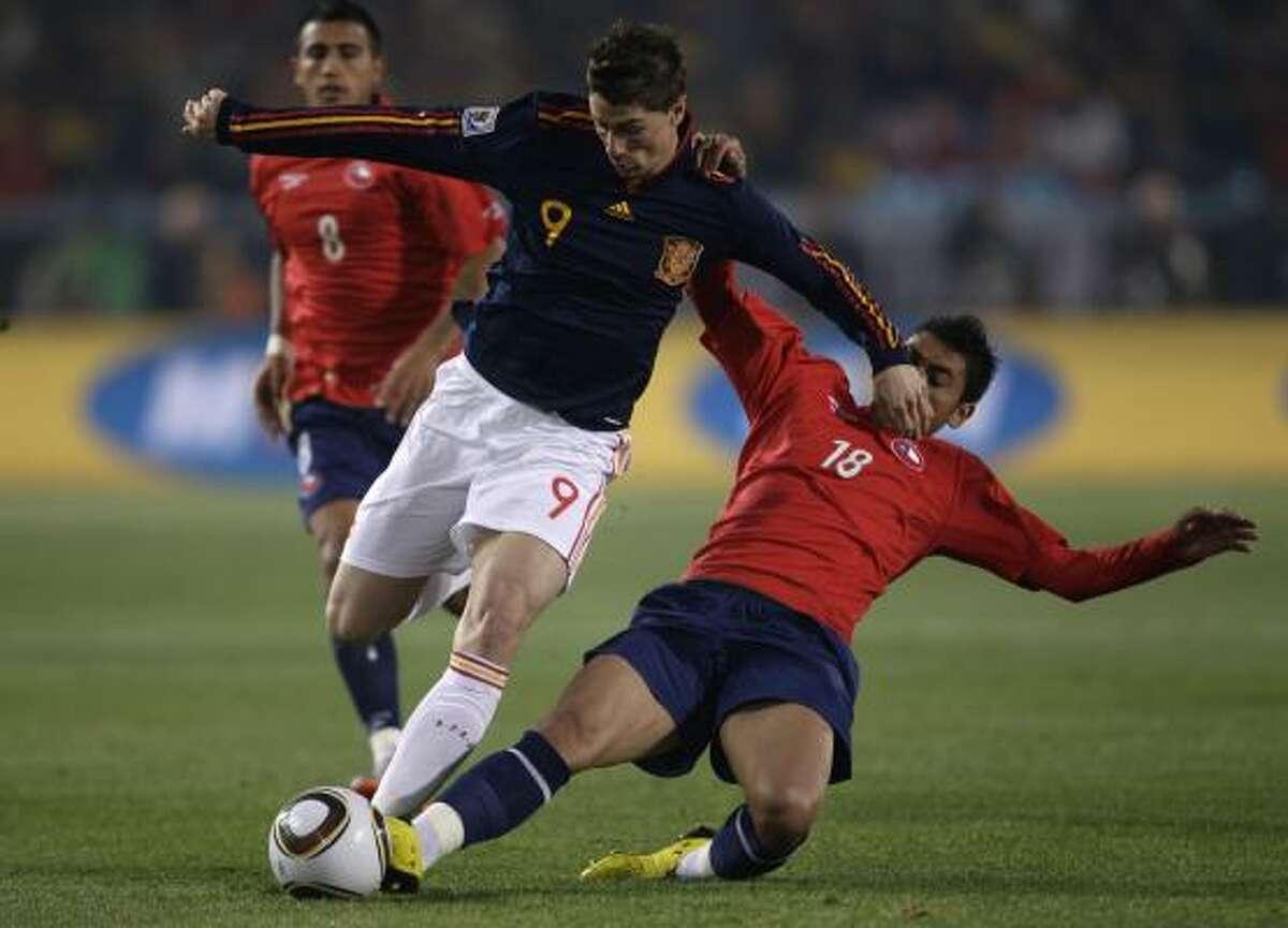 El español Fernando Torres (izq.) protege la pelota ante el acoso del chileno Gonzalo Jara.