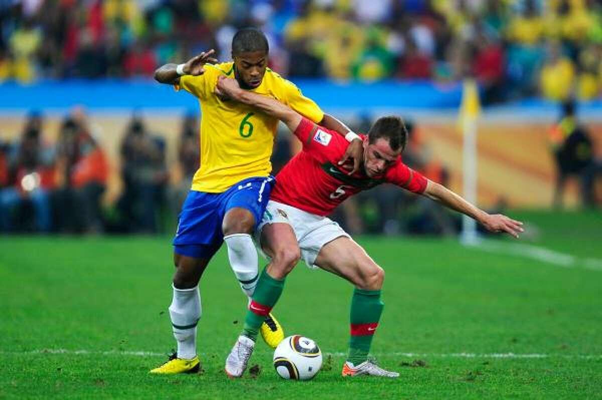 El portugués Duda (der.) cuida el balón ante la marca del brasileño Michel Bastos.