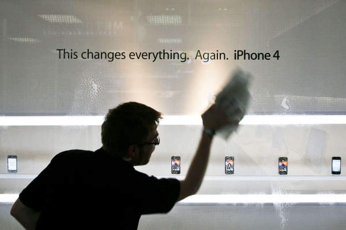 Apple employee, Franklin Weichelt, cleans the glass in front of a display of Apple iPhone 4 phones at the Apple Store in the Memorial City Mall.