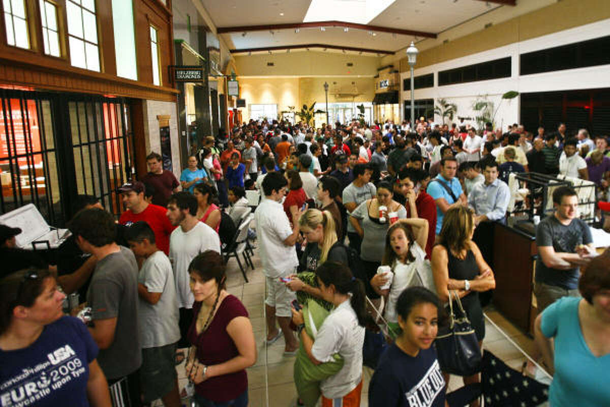 People wait in line for the chance to purchase a new Apple iPhone 4 at the Apple Store in the Memorial City Mall.