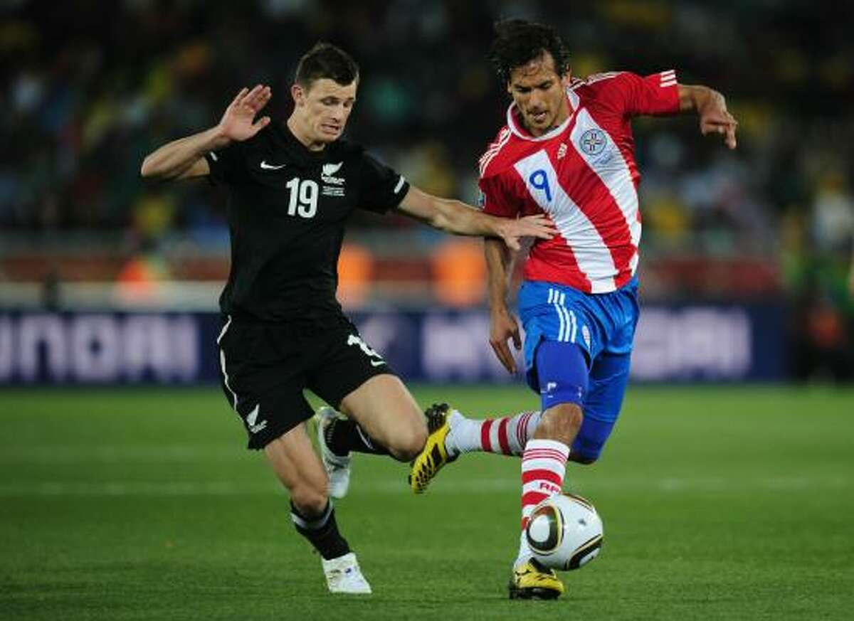 El neocelandés Tommy Smith (izq.) trara de quitarle la pelota al paraguayo Roque Santa Cruz.