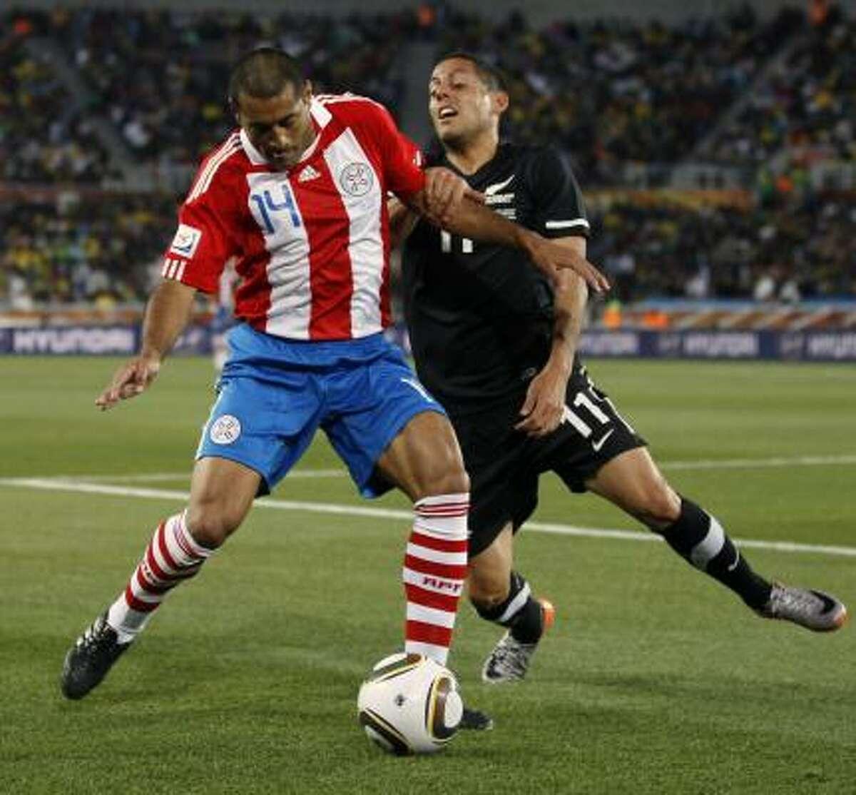 El defensor Paulo Da Silva (izq.) cubre la pelota ante la arremetida del mediocampista Leo Bertos.