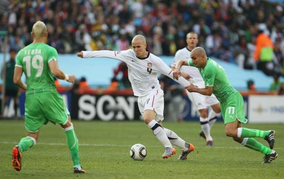 El estadounidense Michael Bradley (centro) escapa de la marca del argelino Rafik Djebbour. Photo: Ian Walton, Getty Images