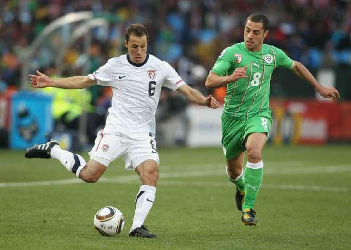 El estadounidense Steve Cherundolo (izq.) tira un centro ante la marca del argelino Medhi Lacen.