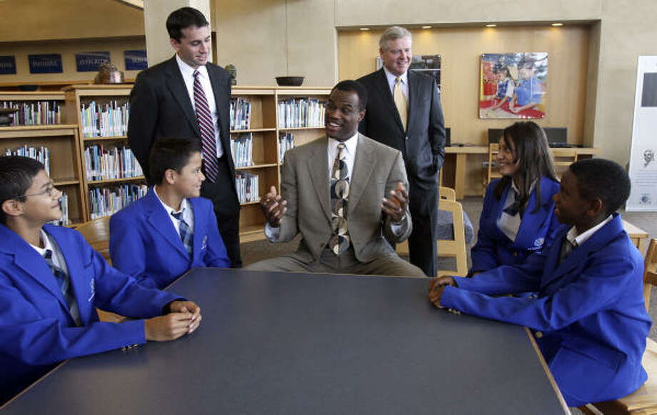 NBA Hall of Famer David Robinson, seated in center, describes his new venture to Carver Academy students on Monday, backed by his partner Daniel Bassichis, left, and T. Patrick Duncan, chairman and CEO of USAA Real Estate Co. Photo: JOHN DAVENPORT, Express_news