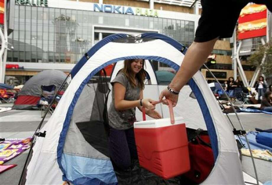 Natasha Monnett, 11, from Castiac, Calif., grabs a cooler handed to her by her dad, Vern, 50, while setting their tent. Photo: Matt Sayles, AP