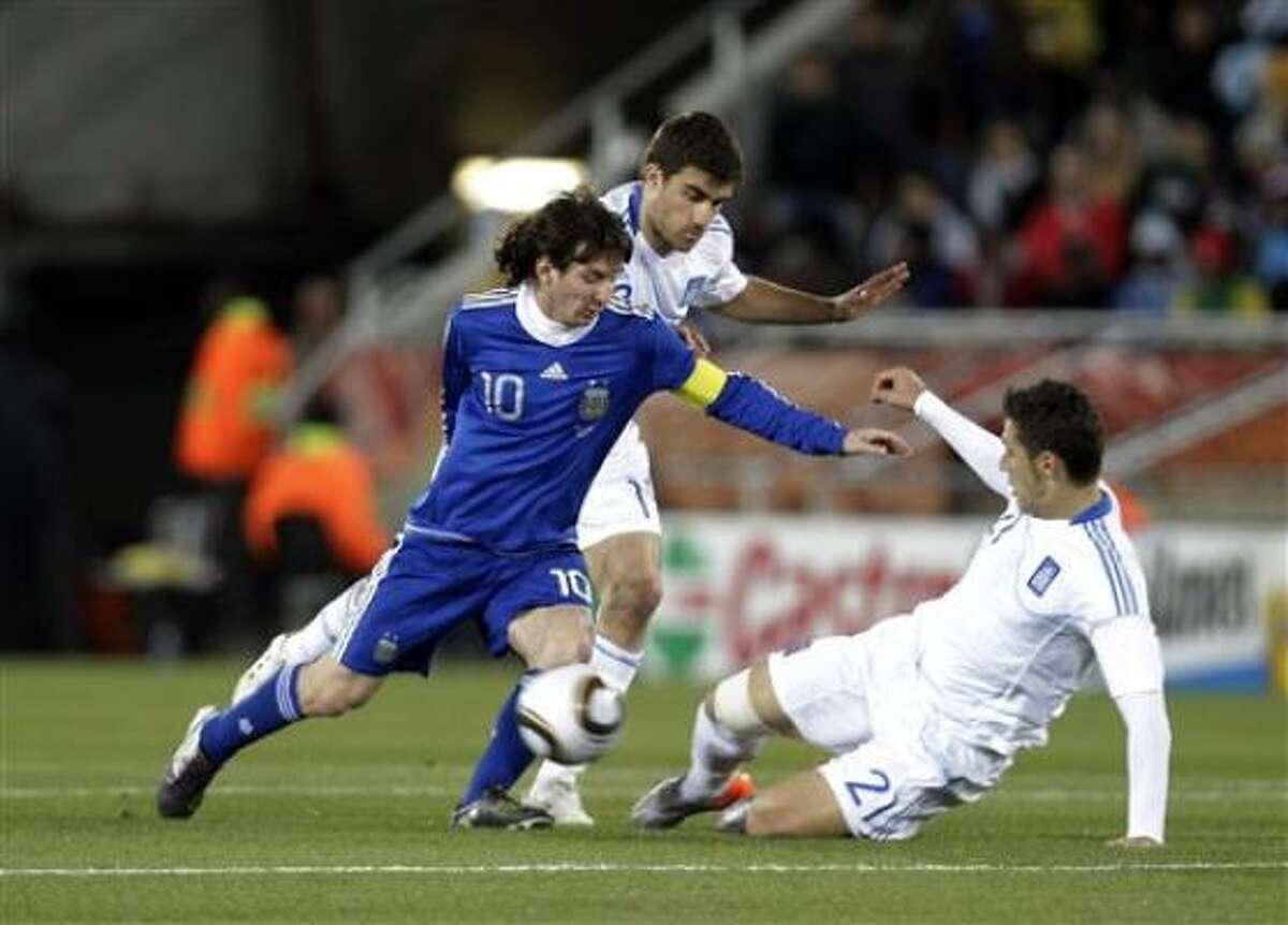 Luciendo por primera vez la cinta de capitán, Lionel Messi trata de dejar en el camino a Sokratis Papastathopoulos y Costas Katsouranis (der) en el partido que Argentina le ganó 2-0 a Grecia en la Copa Mundial.