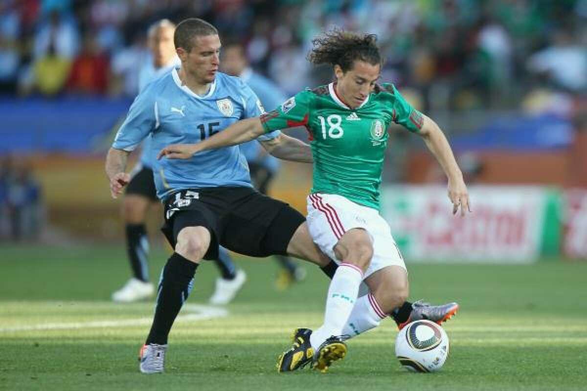 El mediocampista uruguayo Diego Pérez (izq.) trata de quitarle la pelota al mexicano Andrés Guardado.