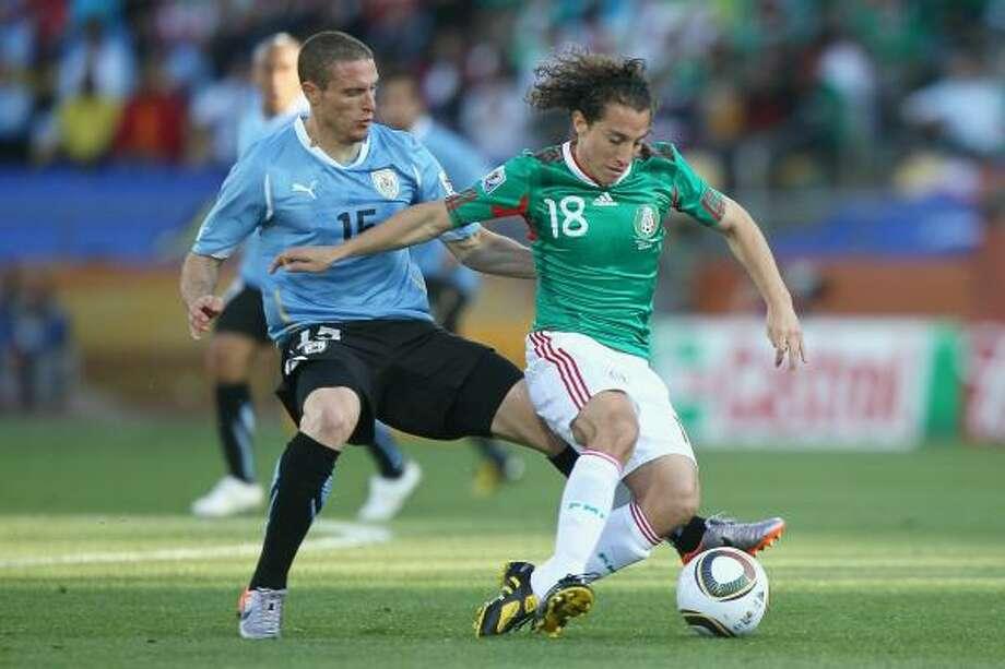 El mediocampista uruguayo Diego Pérez (izq.) trata de quitarle la pelota al mexicano Andrés Guardado. Photo: Christof Koepsel, Getty Images