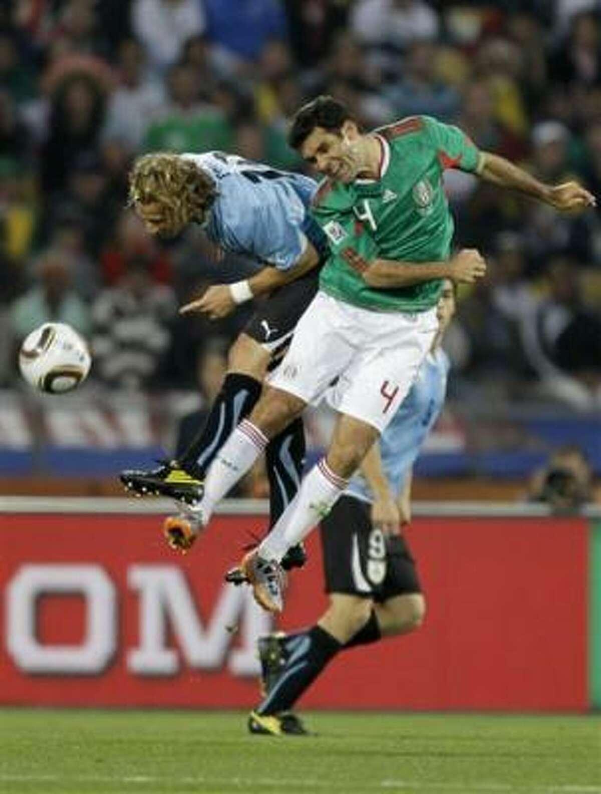 El defensor mexicano Rafael Márquez, a la derecha, y el delantero uruguayo Diego Forlán se disputan un balón en el partido por el Grupo A del Mundial, el martes 22 de junio de 2010.
