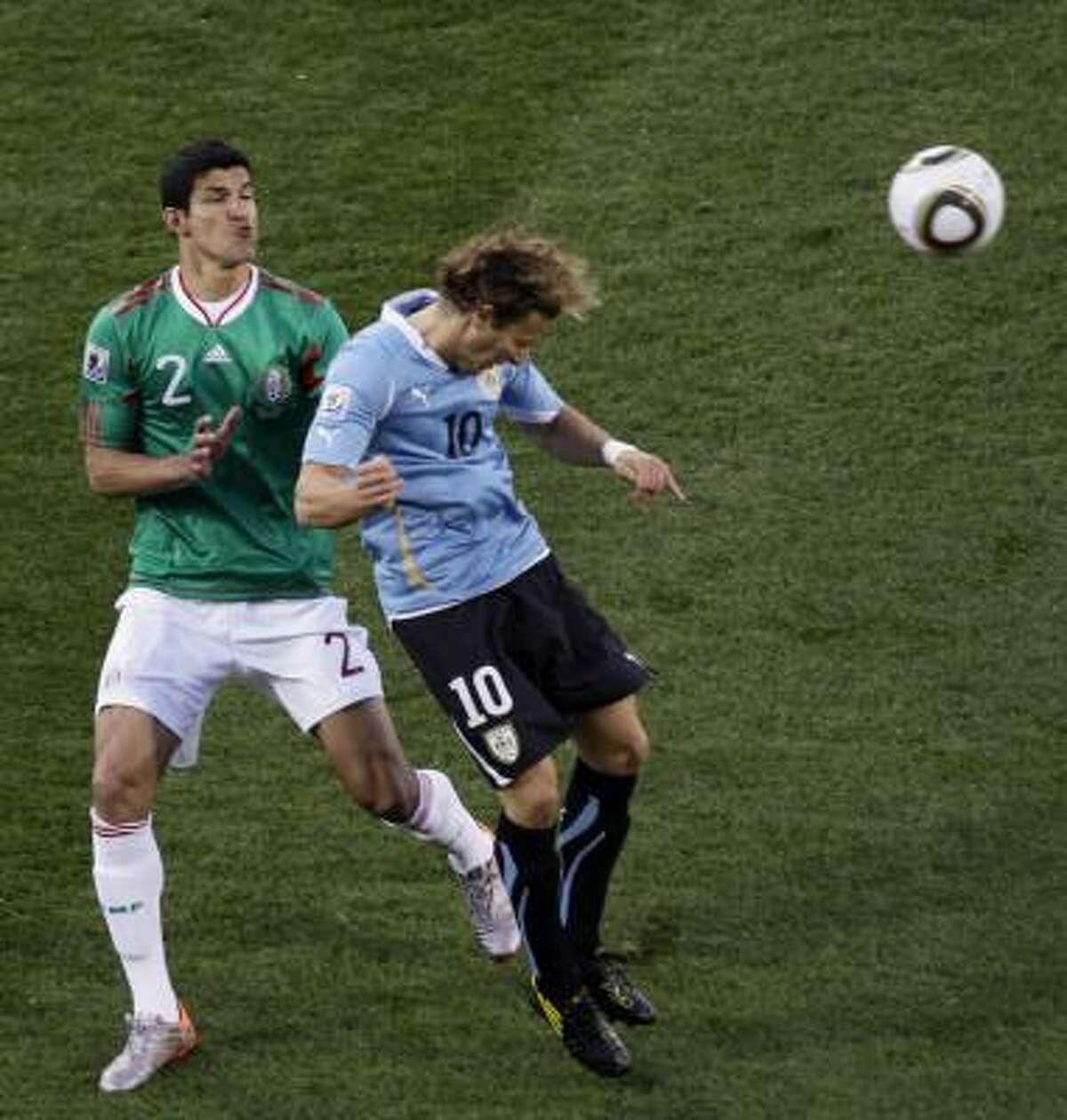 El defensa mexicano Francisco Javier Rodriguez (izq.) marca al delantero uruguayo Diego Forlán.