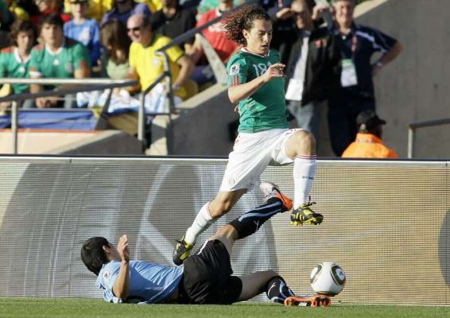 El mediocampista mexicano Guardado (der.) salta ante la barrida de un defensa uruguayo. Photo: Ivan Sekretarev, AP