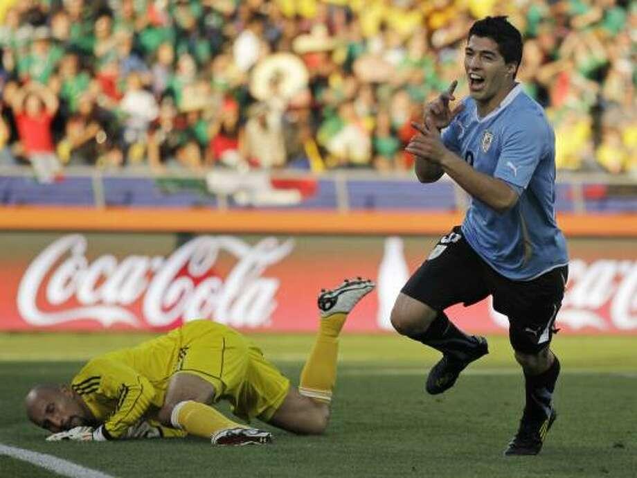 El delantero uruguayo Suárez (der.) corre para celebrar su anotación al equipo mexicano. Photo: Matt Dunham, AP