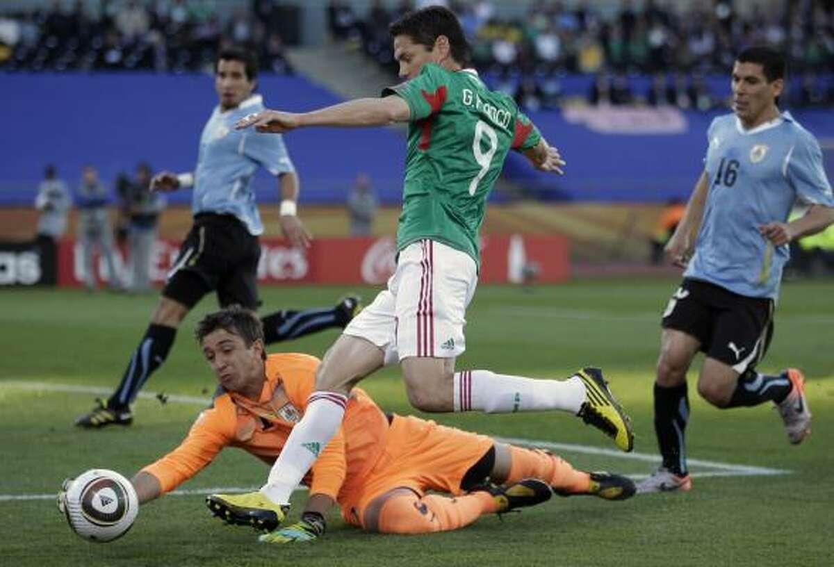 URUGUAY 1, MEXICO 0 Mexico's Guillermo Franco, foreground, can't slip the ball past Uruguay goalkeeper Fernando Muslera at Royal Bafokeng Stadium in Rustenburg.