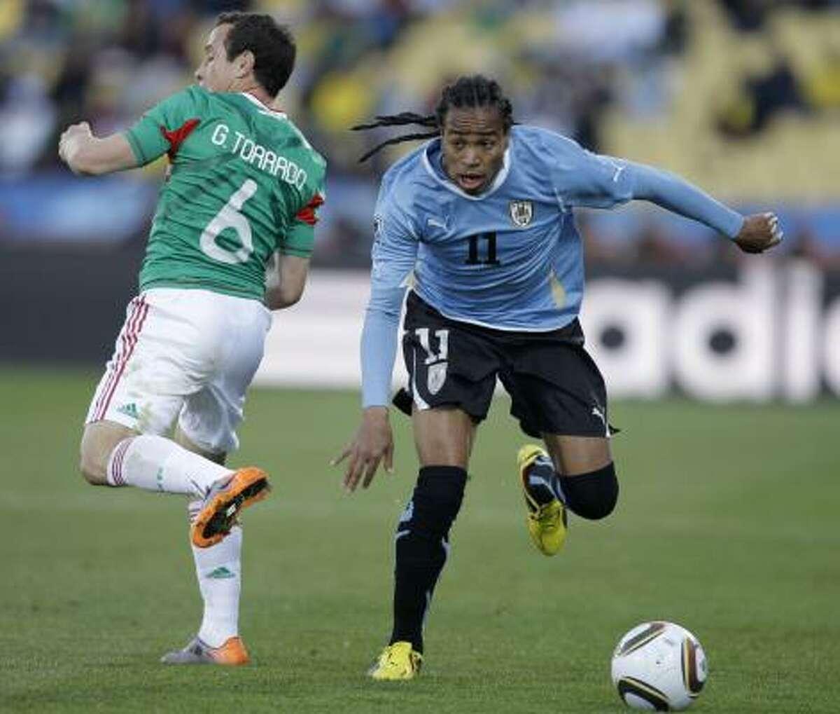 Uruguay's Alvaro Pereira and Mexico's Gerardo Torrado, left, vie for the ball.