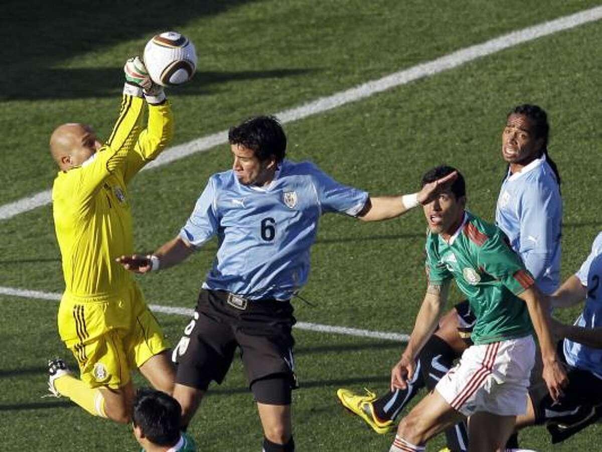 Mexico goalkeeper Oscar Perez, left, punches away the ball next to Uruguay's Mauricio Victorino.