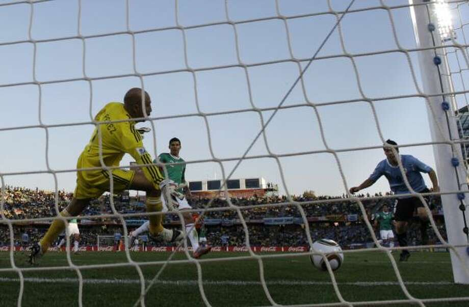 Uruguay's Luis Suarez, right, scores the opening goal against Mexico two minutes before halftime. Photo: Matt Dunham, AP