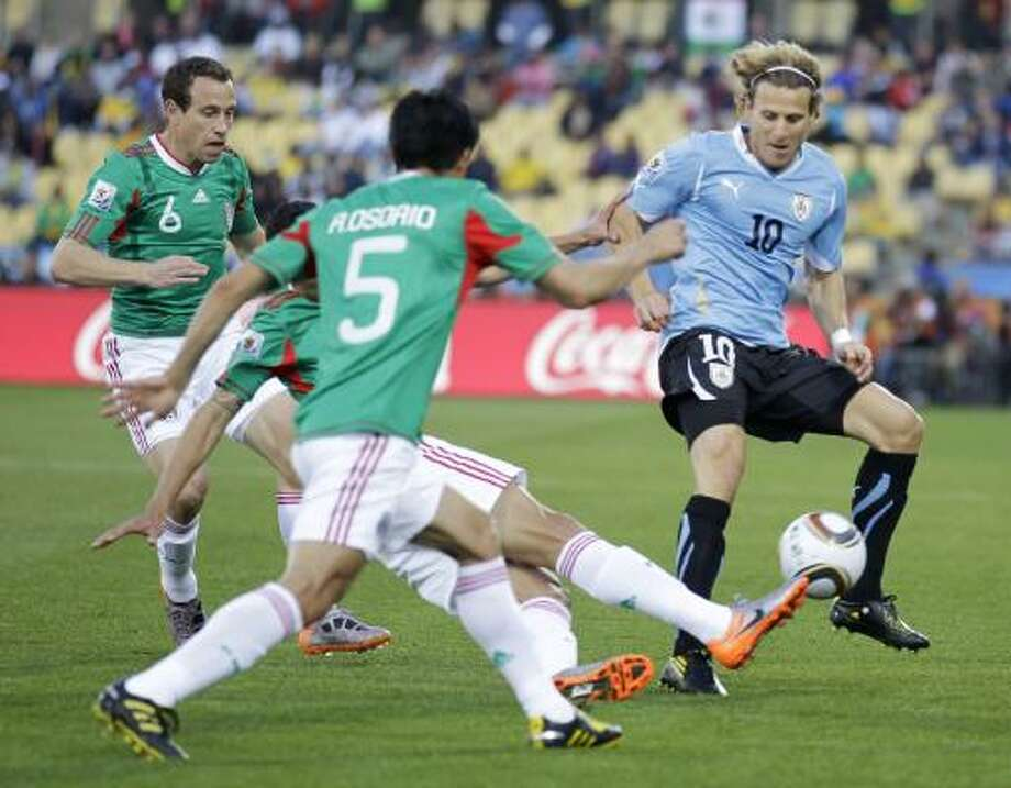 Uruguay's Diego Forlan, right, tries to find a way past Mexico's Gerardo Torrado, left, and Ricardo Osorio. Photo: Matt Dunham, AP