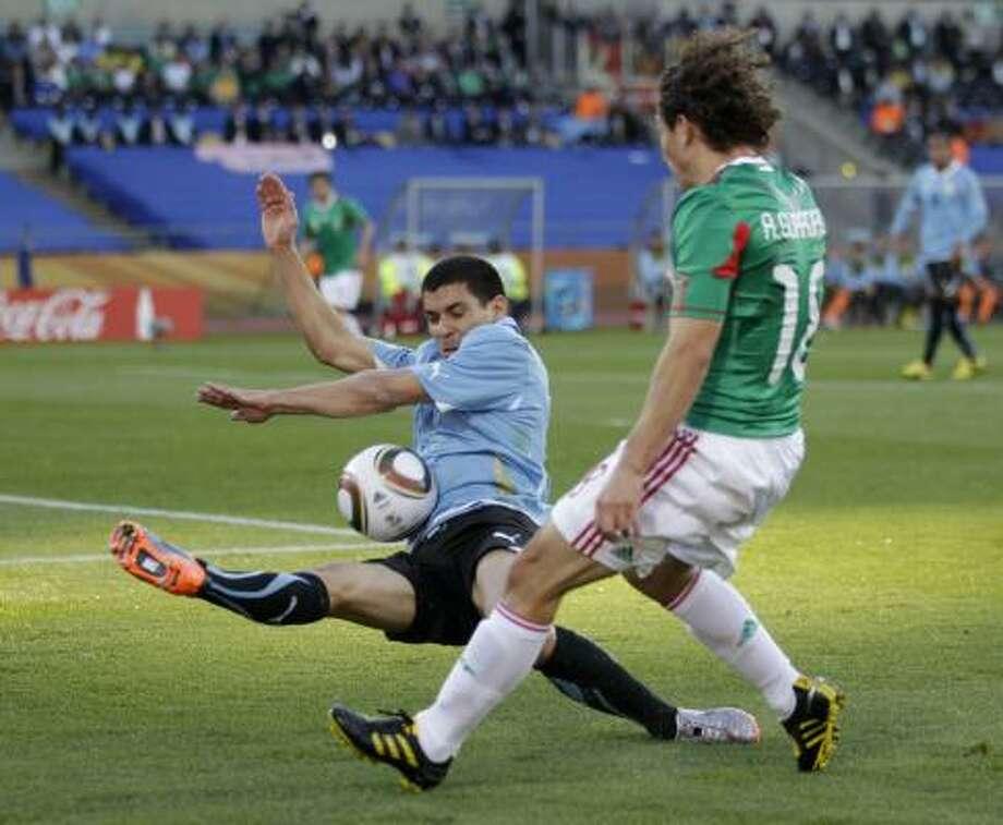 Uruguay's Maximiliano Pereira, left, tries to block a shot by Mexico's Andres Guardado. Photo: Guillermo Arias, AP