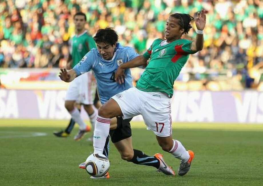 Giovani Dos Santos of Mexico troubles Uruguay with his penetrating runs. Photo: Ezra Shaw, Getty Images