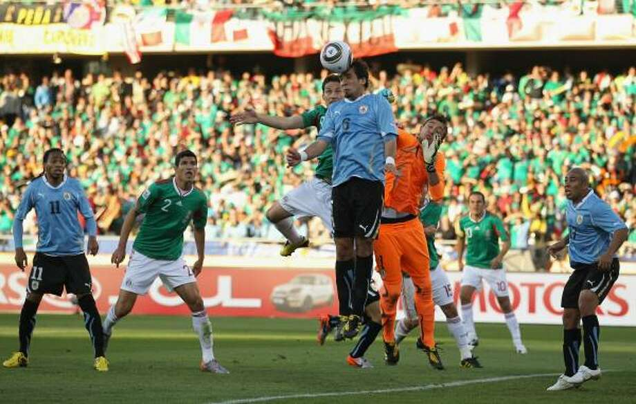 Guillermo Franco of Mexico and Mauricio Victorino of Uruguay jump for the ball. Photo: Ezra Shaw, Getty Images
