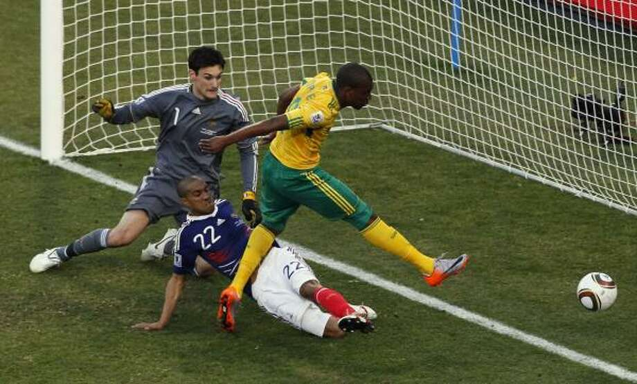 SOUTH AFRICA 2, FRANCE 1 South Africa's Katlego Mphela, right, scores a goal past France goalkeeper Hugo Lloris, left, and France's Gael Clichy, center, at Free State Stadium in Bloemfontein. Photo: Hassan Ammar, AP
