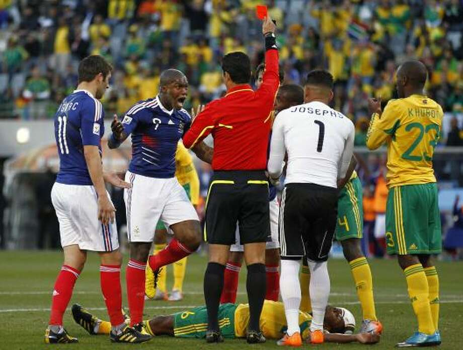 France's Djibril Cisse, second from left, argues with  referee Oscar Ruiz of Colombia, center, after Ruiz awarded a red card to France's Yoann Gourcuff, partially visible at back center, after a brutal foul on South Africa's Macbeth Sibaya. Photo: Francois Mori, AP