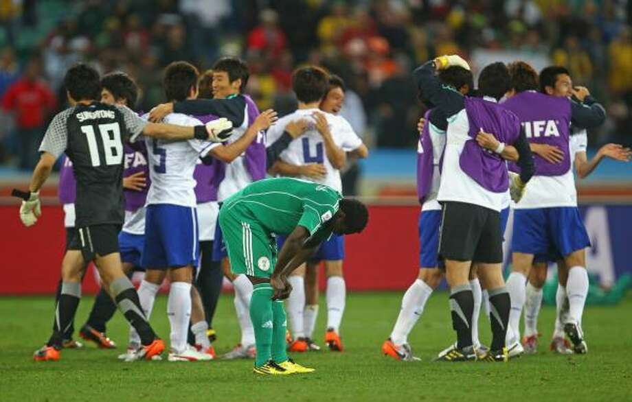 NIGERIA 2, SOUTH KOREA 2 Obafemi Martins of Nigeria is dejected as South Korea players celebrate. The tie was good enough to move them into the second round. Photo: Lars Baron, Getty Images