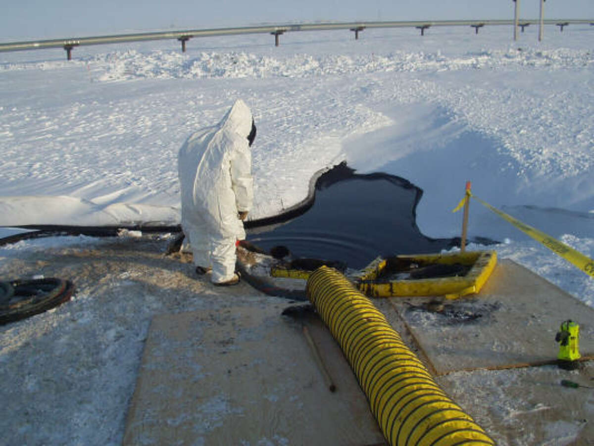 In a photo provided by BP Exploration, workers in environmental suits clean up an oil spill in Prudhoe Bay, Alaska, on March 3, 2006. The leak in the 34-inch diameter line shut down the plant responsible for processing 100,000 barrels of oil per day.