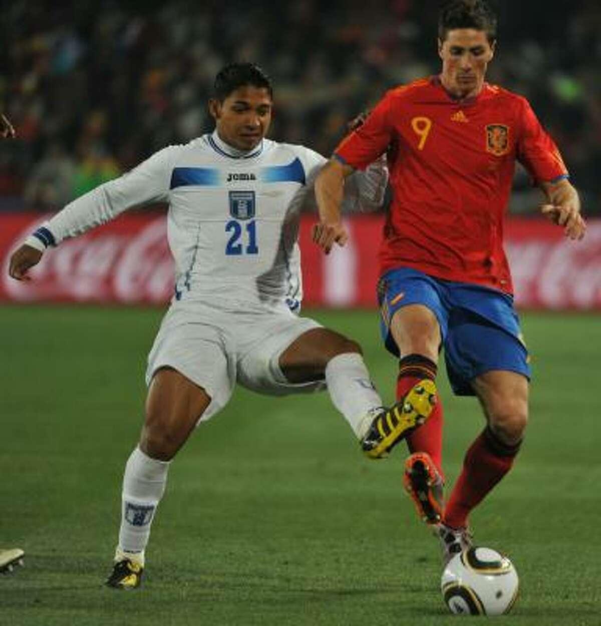 Spain's Fernando Torres, right, holds off Honduras' Emilio Izaguirre.