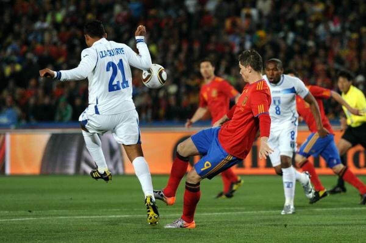 El hondureño Emilio Izaguirre (izq.) trata de robarle un balón al delantero español Fernando Torres.