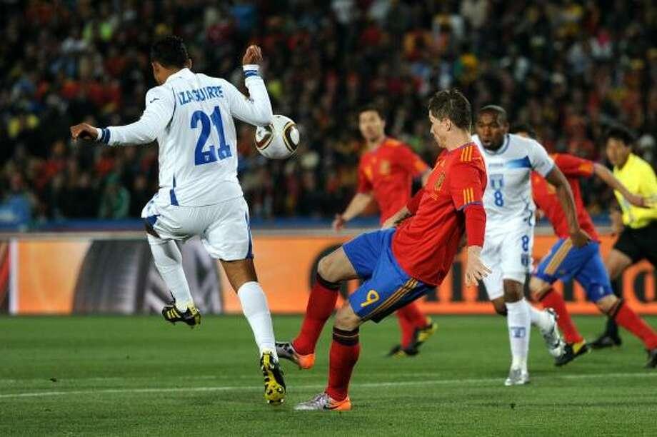 El hondureño Emilio Izaguirre (izq.) trata de robarle un balón al delantero español Fernando Torres. Photo: Jasper Juinen, Getty Images