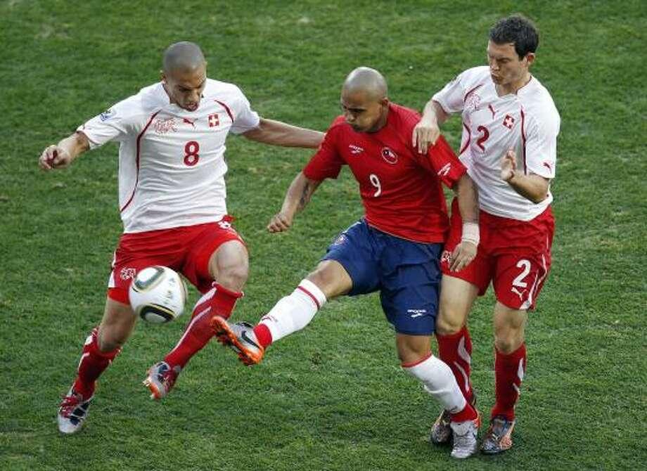 El chileno Humberto Suazo (centro) pelea con los suizos Gokhan Inler (izq.) y Stephan Lichtsteiner. Photo: Hassan Ammar, AP