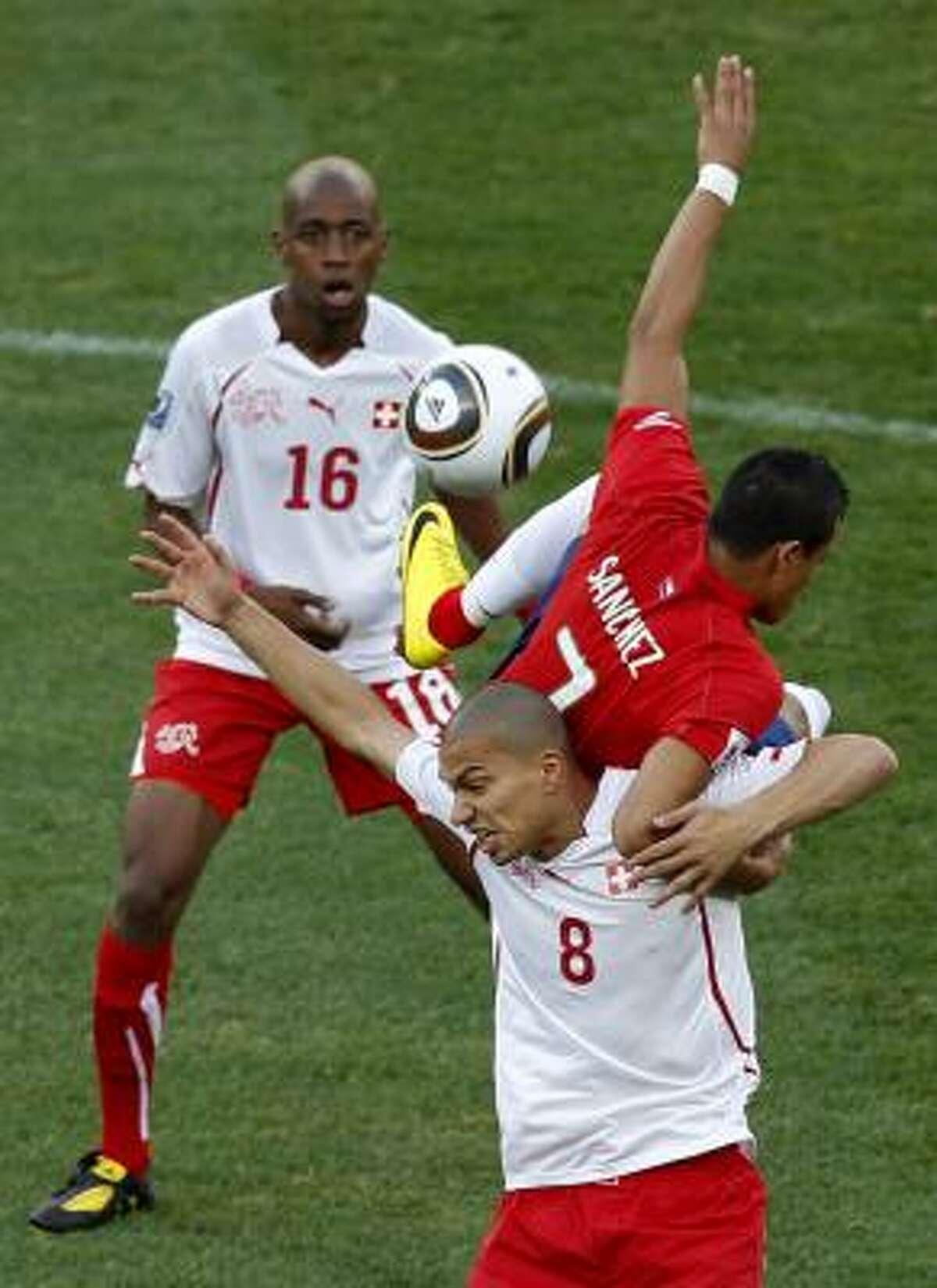 El chileno Alexis Sánchez (7) busca un balón aéreo con el suizo Inler.