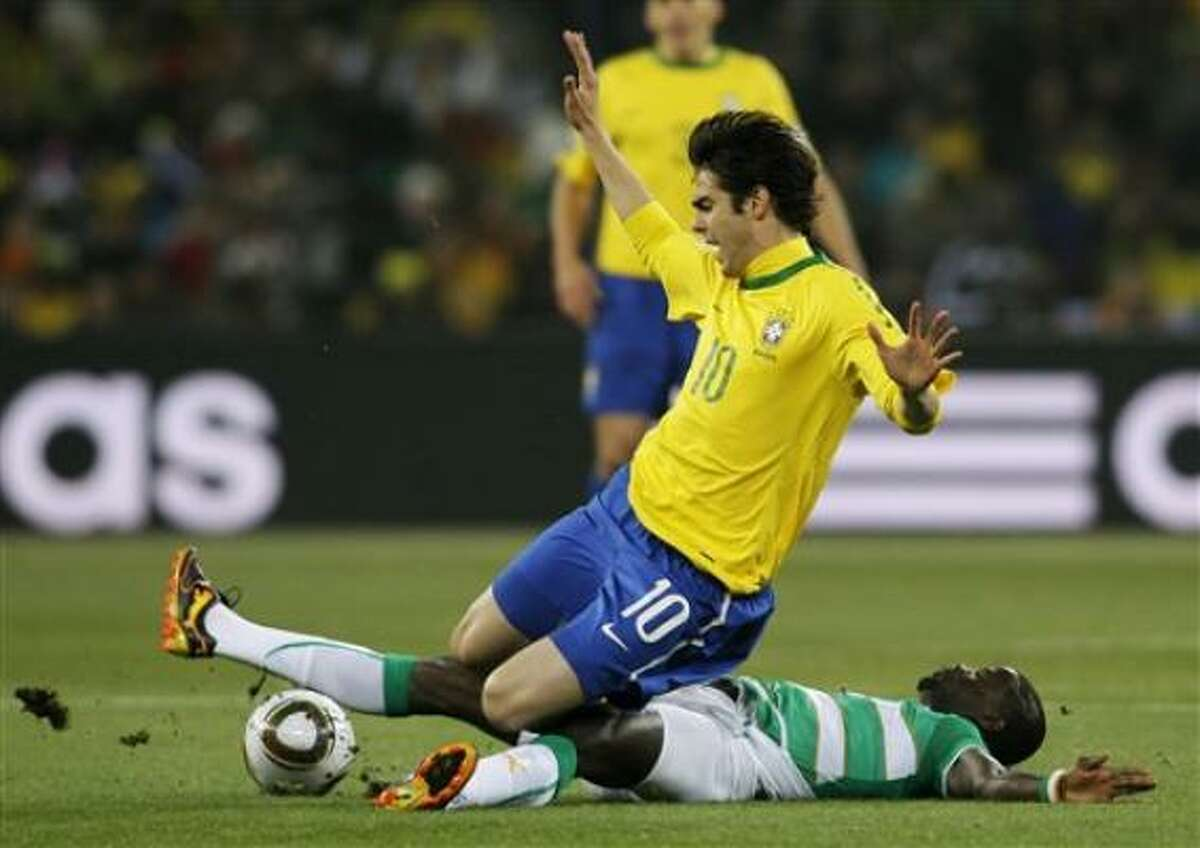 El marfileño Emmanuel Eboue se barre ante el avance del brasileño Kaká en el partido por el Grupo G del Mundial el domingo 20 de junio de 2010.