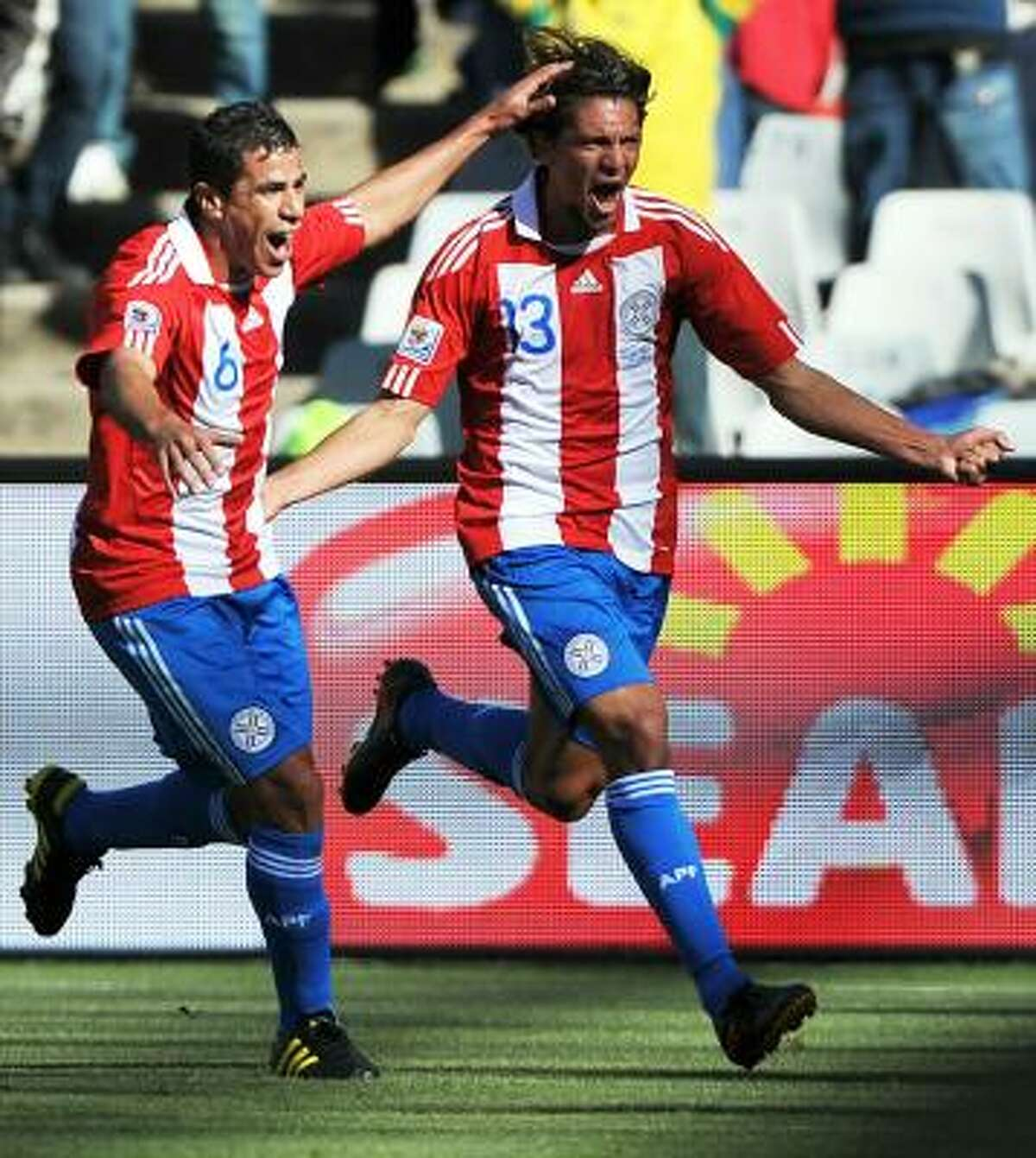 Paraguay midfielder Enrique Vera, right, celebrates his goal with midfielder Carlos Bonet.
