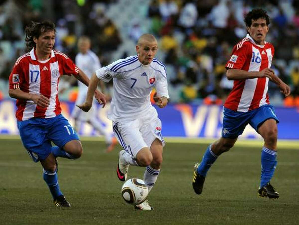 Slovakia midfielder Vladimir Weiss, center, fights for the ball with Paraguay defender Aureliano Torres, left, and midfielder Cristian Riveros.