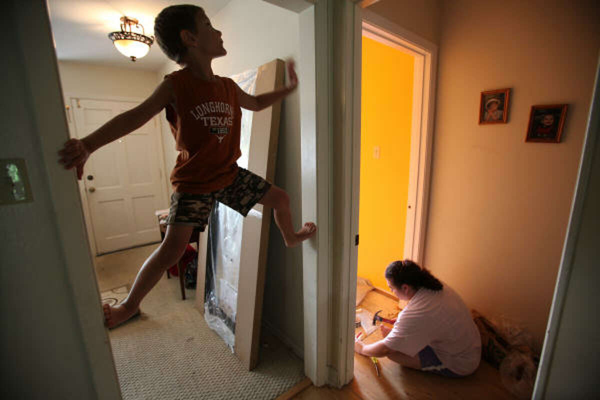 James Hanus, 6, climbs the door frame while his mother Brandy Hanus attempts to put down a wood floor in her 13-year-old daughter Megan Hanus' bedroom in Houston. Her husband, Sgt. Bernie Hanus, has been deployed in Iraq for seven months, and she is remodeling Megan's room all by herself as a surprise to her husband.