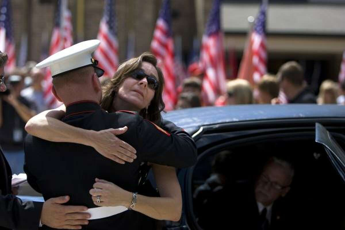 Marine Sgt. Ryan Lenser tries to comfort Melissa Whitney, Sgt. Brandon Bury's aunt, outside St. Martha Catholic Church in Kingwood, where a memorial service was held.