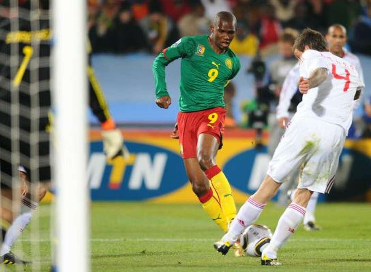 Cameroon striker Samuel Eto'o is challenged for the ball by Denmark's Daniel Agger.