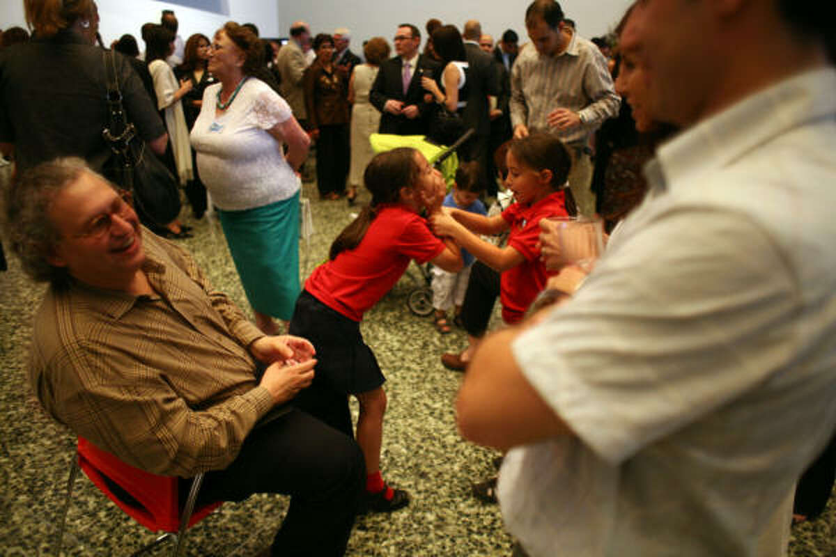 Martin Rubinstein (left) chats with Leonardo Rivas (right) while Rubinstein's daughters Camila (center right) and Sophia (center left), play as local Argentineans gathered to celebrate Argentina's Independence Day and bicentennial at the Museum of Fine Arts Houston Tuesday, May 25, 2010, in Houston.