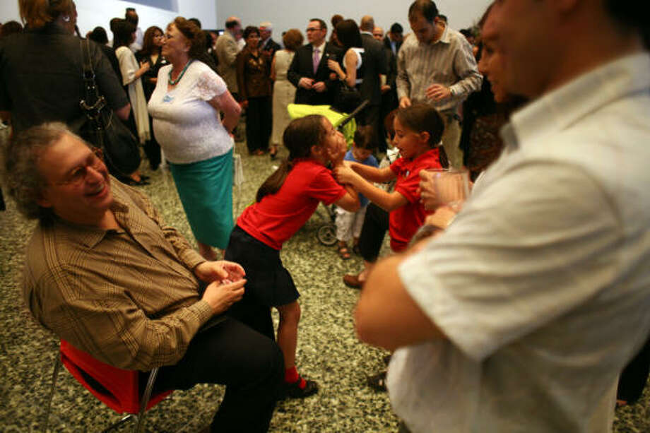 Martin Rubinstein (left) chats with Leonardo Rivas (right) while Rubinstein's daughters Camila (center right) and Sophia (center left), play as local Argentineans gathered to celebrate Argentina's Independence Day and bicentennial at the Museum of Fine Arts Houston Tuesday, May 25, 2010, in Houston. Photo: Johnny Hanson, Chronicle